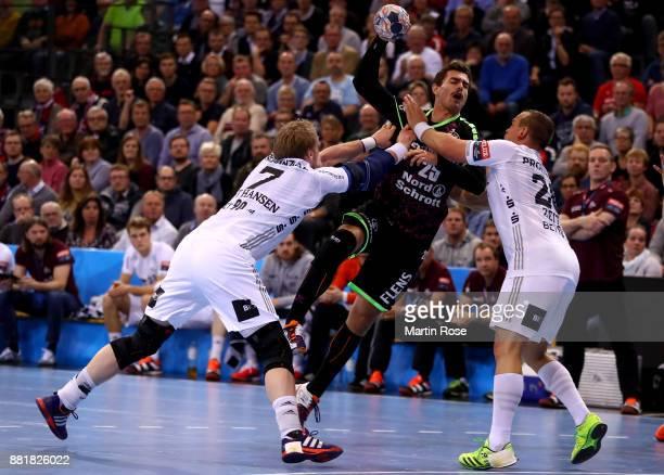 Rasmus Lauge of Flensburg Handewitt challenges Rene Toft Hansen and Christian Zeitz of Kiel for the ball during the Velux EHF Champions League match...