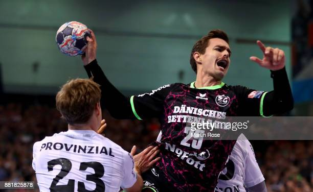 Rasmus Lauge of Flensburg Handewitt challenges Rune Dahmke of Kiel for the ball during the Velux EHF Champions League match between SG Flensburg...
