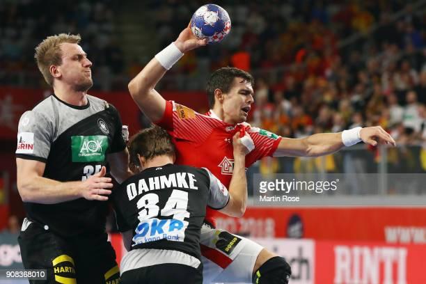 Rasmus Lauge Schmidt of Denmark is challenged by Rune Damke and Julius Kuehn of Germany during the Men's Handball European Championship main round...