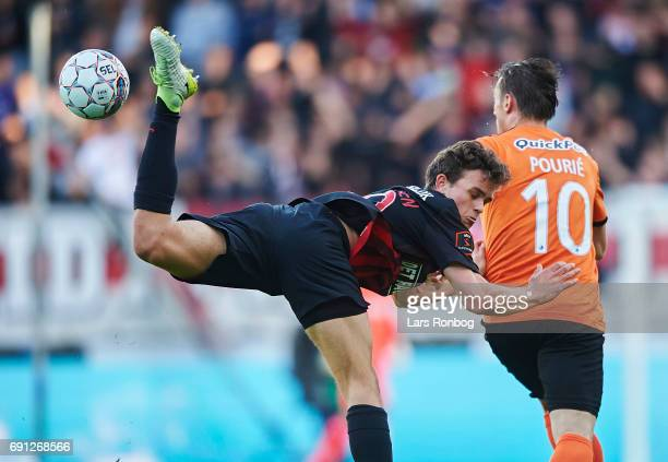Rasmus Nicolaisen of FC Midtjylland and Marvin Pourie of Randers FC compete for the ball during the Danish Alka Superliga Europa League Playoff match...