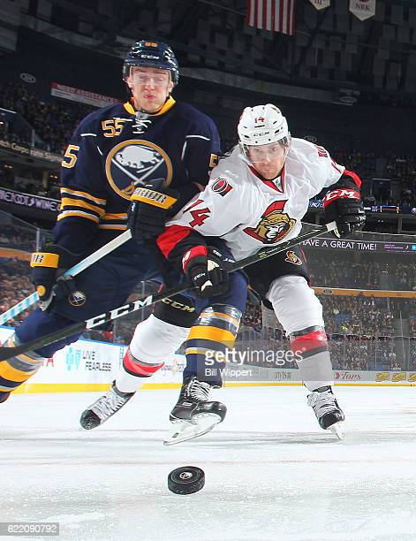 Rasmus Ristolainen of the Buffalo Sabres and Mike Blunden of the Ottawa Senators battle for the puck during an NHL game at the KeyBank Center on...