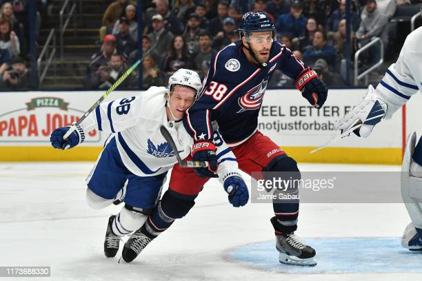 Rasmus Sandin of the Toronto Maple Leafs and Boone Jenner of the Columbus Blue Jackets battle for position during the third period of a game on...