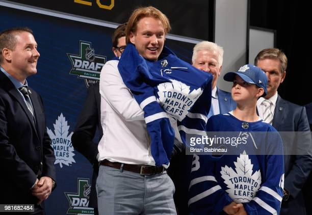 Rasmus Sandin puts on a Toronto Maple Leafs jersey after being selected twentyninth overall by the Toronto Maple Leafs during the first round of the...