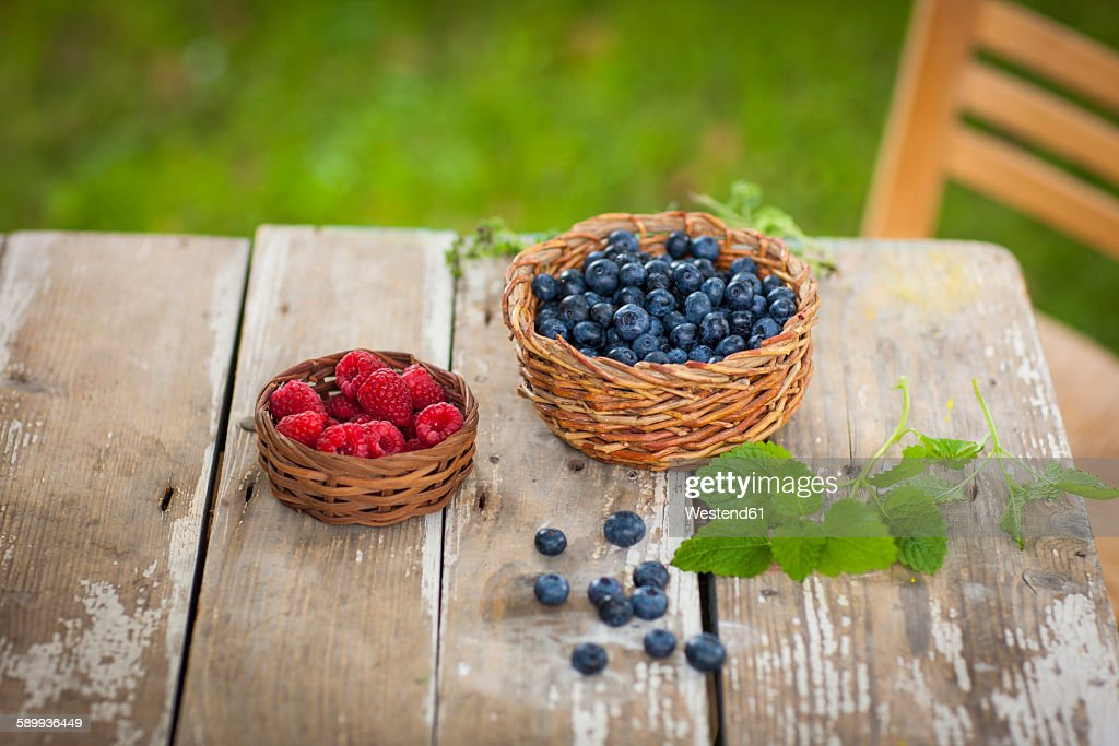 Raspberries and blueberries in baskets : Stock Photo