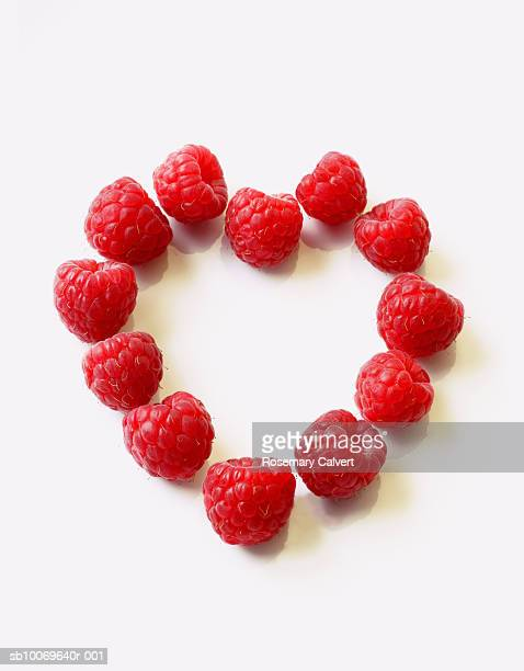 Raspberries arranged to form heart shape on white background