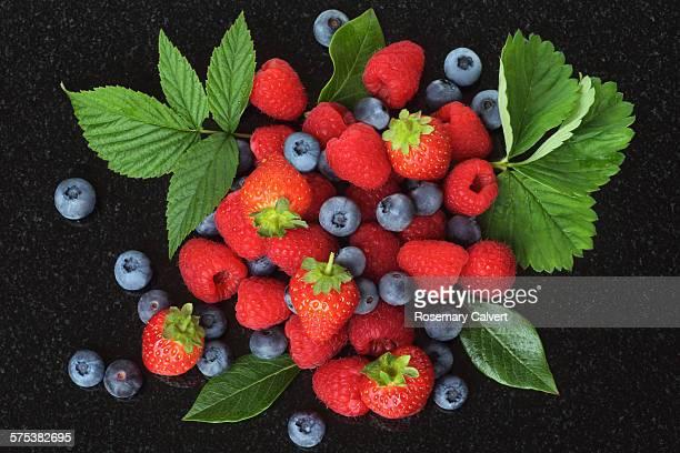 raspberries, blueberries and strawberries on black - ベリー類 ストックフォトと画像