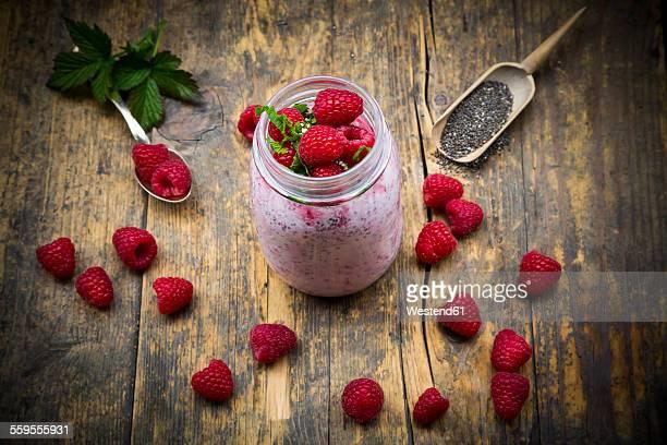 Raspberries, chia, milk, kiwi, hemp seed and mint in a glass