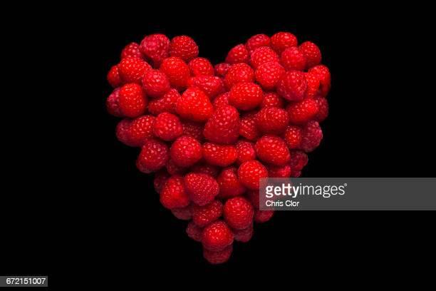 Raspberries in shape of heart on black background