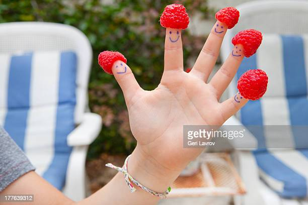 Raspberries on child's fingers with happy faces