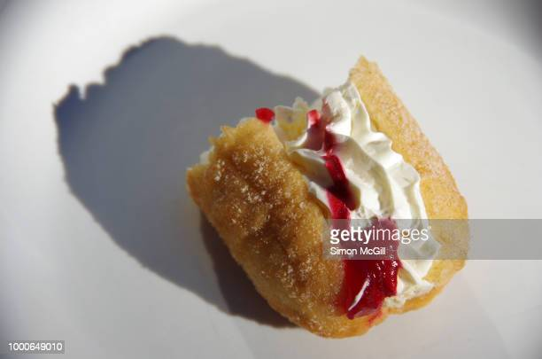 Raspberry jam and cream donut with bites taken out of it on a white plate