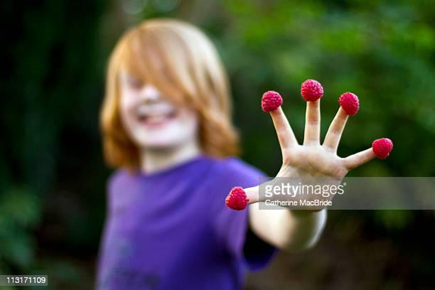 raspberry on finger - catherine macbride stockfoto's en -beelden