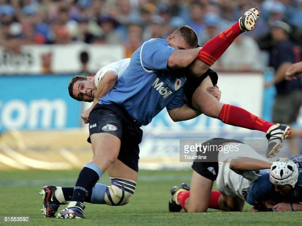 Rassie Erasmus of the Cheetahs is tackled by Kees Lensing of the Bulls during the ABSA Currie Cup Final between the Blue Bulls and the Cheetahs at...