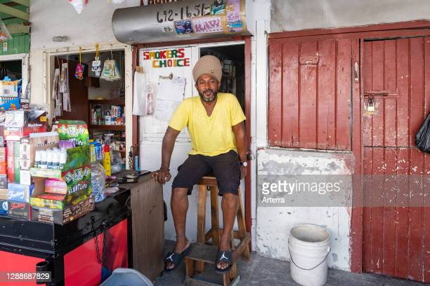 Rastafari shopkeeper / Rasta vendor selling groceries in shopping street in the city Georgetown, Demerara-Mahaica region, Guyana, South America.