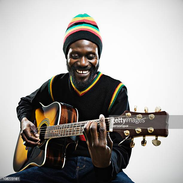 rastafarian man playing guitar - reggae stock photos and pictures