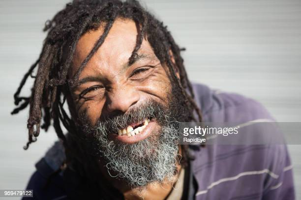 rastafarian with missing teeth laughs - homeless stock photos and pictures
