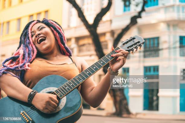 rastafarian woman playing acoustic guitar - early rock & roll stock pictures, royalty-free photos & images