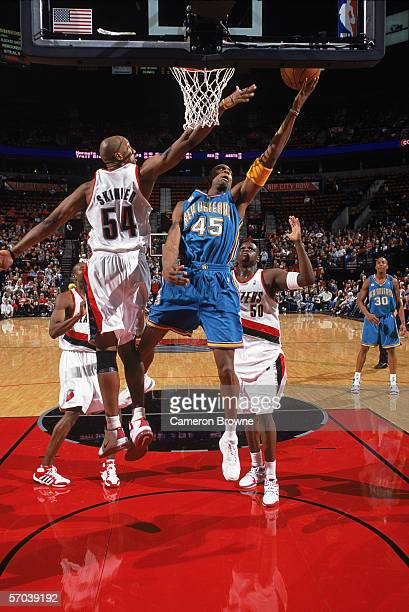 Rasual Butler of the New Orleans Hornets takes the ball to the basket against Brian Skinner and Zach Randolph of the Portland Trail Blazers during...