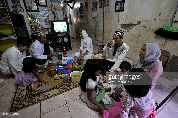 Rasyid an Indonesian fisherman and wife Sukaisih entertain relatives at their residence in Jakarta to celebrate EidalFitr on August 31 2011 The...