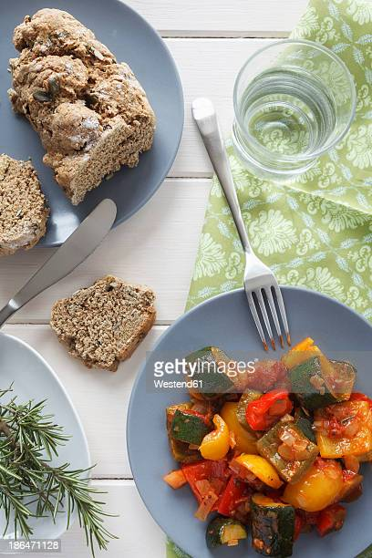 Ratatouille on plate besides bread slice and rosemary on table