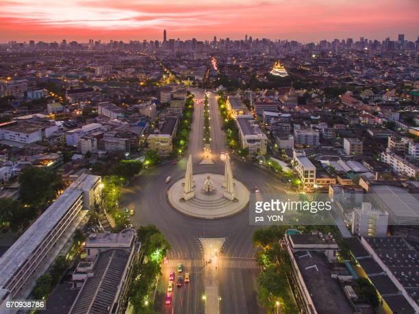 ratchadamnoen road and democracy monument in bangkok, thaialnd in twilight - ラチャダムリ通り ストックフォトと画像
