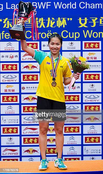 Ratchanok Intanon of Thailand poses on the podium with the trophy after winning her women's singles final match against Li Xuerui of China during the...