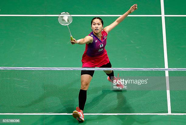 Ratchanok Intanon of Thailand returns a shot to Sayaka Sato of Japan during their women's singles match at the 2016 Badminton Asia Championships in...