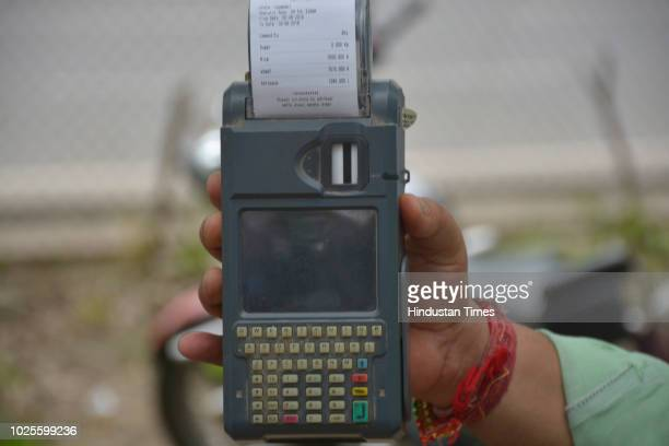 A ration dealer shows handheld Echallan machine during a protest by ration dealers at district headquarters demanding scarping of FIRs against them...