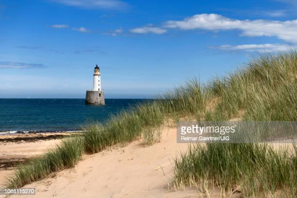 rattray head lighthouse in the north sea at buchan aberdeenshire scotland with sea grass on sand dunes and sandy beach - rattray head stock pictures, royalty-free photos & images