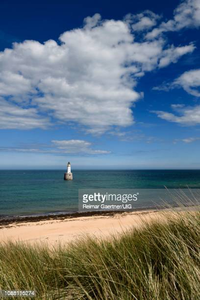 rattray head lighthouse in the north sea at buchan aberdeenshire scotland with blue sky and white cloud from sea grass sand dunes - rattray head stock pictures, royalty-free photos & images