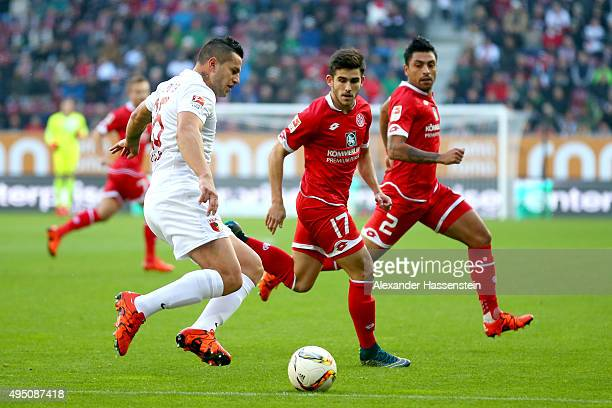 Raul Bobadilla of Augsburg battles for the ball with Jairo Samperio Bustara of Mainz and his team mate Gonzalo Alejandro Jara Reyes during the...