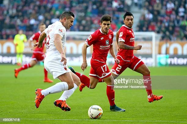 Raul Bobadilla of Augsburg battles for the ball with Jairo Samperio Bustara of Mainz and his team mate Gonzalo Alejandro Jara Reyes during the...