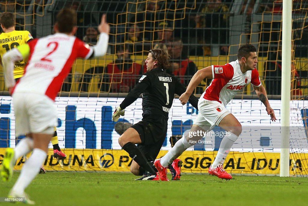 Raul Bobadilla of Augsburg celebrates scoring the opening goal whilst Roman Weidenfeller, keeper of Dortmund looks dejected during the Bundesliga match between Borussia Dortmund and FC Augsburg at Signal Iduna Park on February 4, 2015 in Dortmund, Germany.