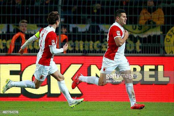Raul Bobadilla of Augsburg celebrates scoring the opening goal with his team mate Paul Verhaegh during the Bundesliga match between Borussia Dortmund...
