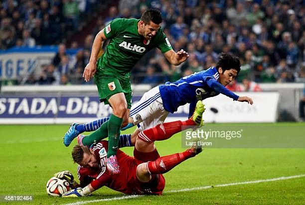 Raul Bobadilla of Augsburg is challenged by Ralf Fahrmann of Schalke 04 and Atsuto Uchida of Schalke 04 during the Bundesliga match between FC...