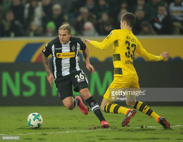 Raul Bobadilla of Moenchengladbach and Julian Weigl of Dortmund battle for the ball during the Bundesliga match between Borussia Moenchengladbach and...