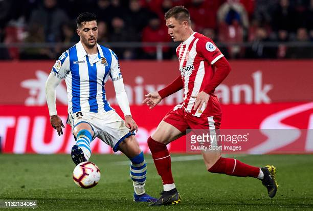 Raul Carnero of Girona FC competes for the ball with Mikel Merino of Real Sociedad during the La Liga match between Girona FC and Real Sociedad at...