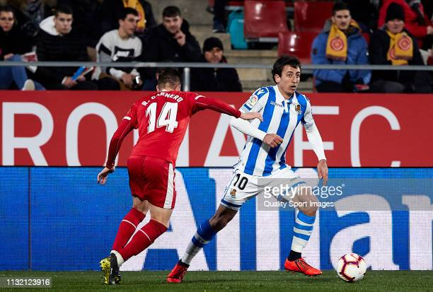 Raul Carnero of Girona FC competes for the ball with Mikel Oyarzabal of Real Sociedad during the La Liga match between Girona FC and Real Sociedad at...