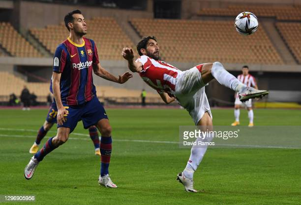 Raul Garcia of Athletic Bilbao is challenged by Sergio Busquets of Barcelona during the Supercopa de Espana Final match between FC Barcelona and...