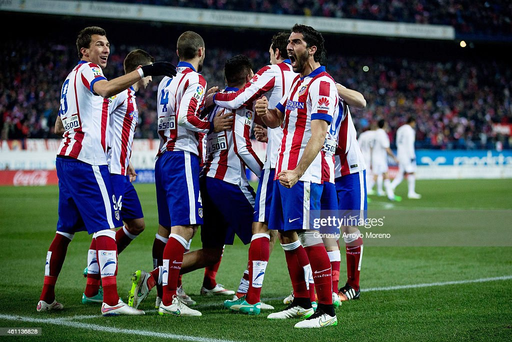 Raul Garcia (R) of Atletico de Madrid celebrates his team,s second goal scored by Jose Maria Gimenez (4thL) with teammates as Mario Mandzukic (L) during the Copa del Rey Round of 16 first leg match between Club Atletico de Madrid and Real Madrid CF at Vicente Calderon Stadium on January 7, 2015 in Madrid, Spain.