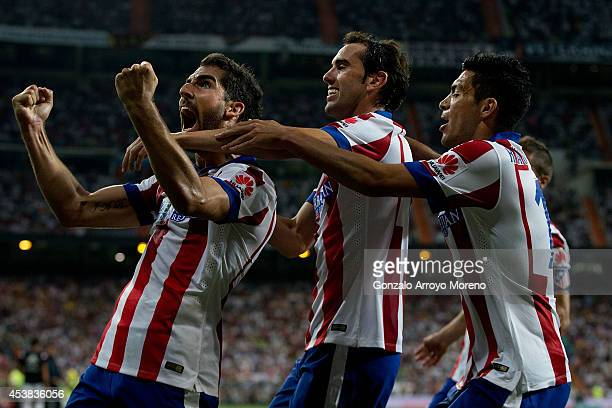 Raul Garcia of Atletico de Madrid celebrates scoring the opening goal with teammates Diego Godin and Raul Jimenez during the Supercopa first leg...