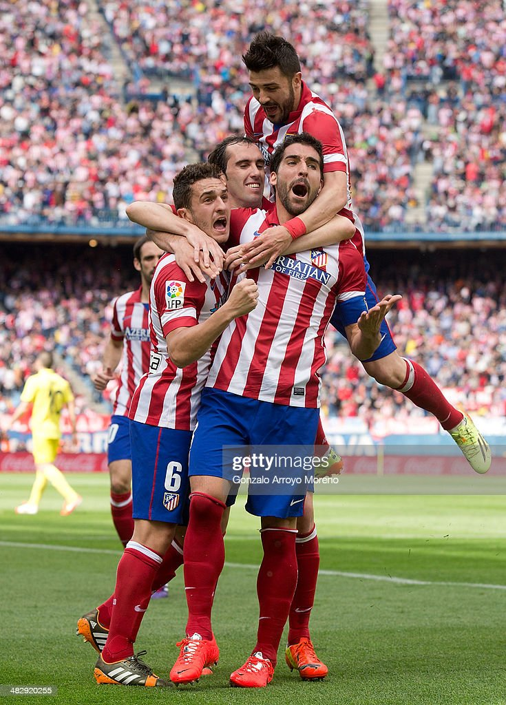 Raul Garcia (2ndR) of Atletico de Madrid celebrates scoring their opening goal with teammates Koke (L), Diego Godin (2ndL)David Villa (3dL) during the La Liga match between Club Atletico de Madrid and Villarreal CF at Vicente Calderon Stadium on April 5, 2014 in Madrid, Spain.