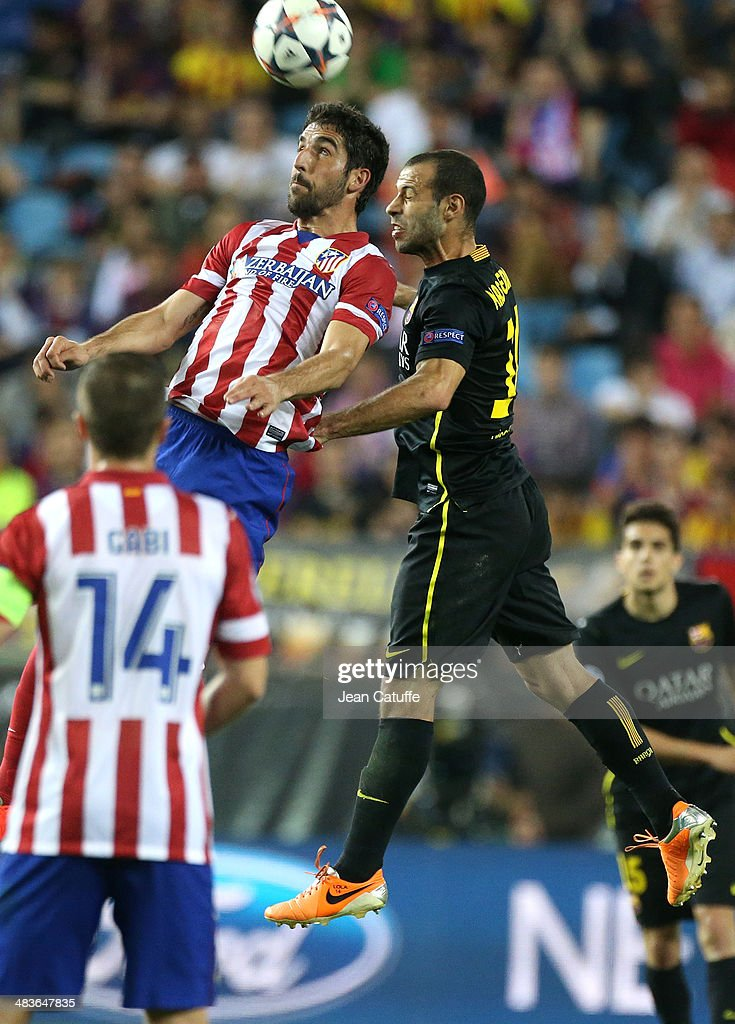 Raul Garcia of Atletico Madrid and Javier Mascherano of FC Barcelona in action during the UEFA Champions League quarter final match between Club Atletico de Madrid and FC Barcelona at Vicente Calderon stadium on April 9, 2014 in Madrid, Spain.