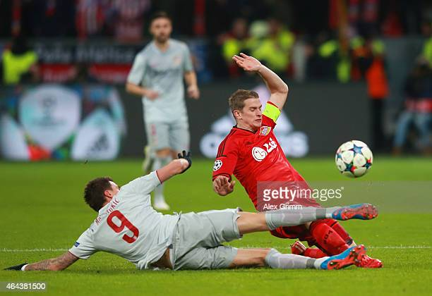 Raul Garcia of Atletico Madrid tackles Lars Bender of Bayer Leverkusen during the UEFA Champions League round of 16 match between Bayer 04 Leverkusen...