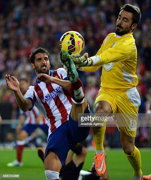 Raul Garcia of Atletico Madrid vies with Juan Carlos of Cordoba during the La Liga match between Atletico Madrid and Cordoba at Vicente Calderon...