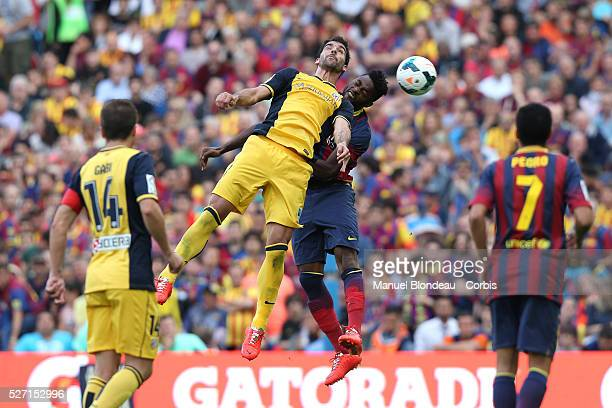 Raul Garcia of Club Atletico de Madrid duels for the ball with Alex Song of FC Barcelona during the La Liga football match between FC Barcelona and...