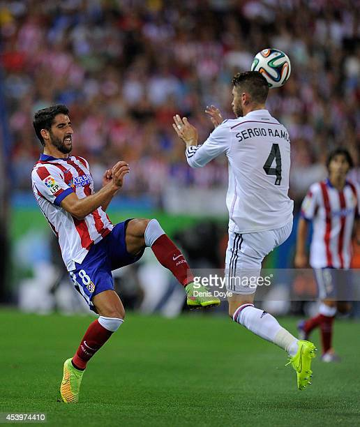 Raul Garcia of Club Atletico de Madrid tackles Sergio Ramos of Real Madrid during the Supercopa second leg match between Club Atletico de Madrid and...