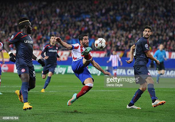 Raul Garcia of Club Atletico de Madrid tries to shoot past Alberto Botia of Olympiacos FC during the UEFA Champions League Group A match between Club...