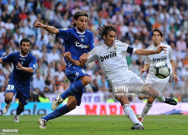 Raul Gonzalez of Real Madrid duels for the ball with David Prieto of Xerez during the La Liga match between Real Madrid and Xerez at the Estadio...