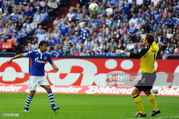 Raul Gonzalez of Schalke scores his teams fourth goal over goalkeeper Michael Rensing of Koeln during the Bundesliga match between FC Schalke 04 and...