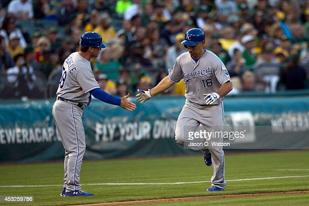 Raul Ibanez of the Kansas City Royals is congratulated by third base coach Mike Jirschele after hitting a home run against the Oakland Athletics...